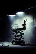 Worker sandblasting an interior wall in a warehouse.