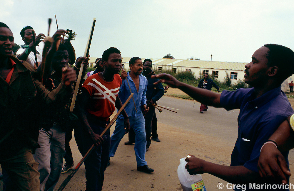 Ratanda township, Heidelberg, Transvaal, South Africa, 1992. Inkatha Freedom Party warriors get splashed with Intelezi imuti or war potion as they prepare to confromnt ANC supporters  during clashes between ANC supporting residents and Inkatha Freedom party supporters from the hostel.