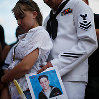 Keith Hoover (L) and Monica Matryba pray while they hold a photo of friend Jon Blunk, killed while protecting his girlfriend in the Century theater shootings on July 20, 2012 at a prayer vigil for the victims in Aurora, Colorado July 22, 2012. REUTERS/Rick Wilking (UNITED STATES)