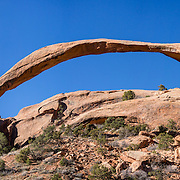 Landscape Arch, on Devils Garden Trail, Arches National Park, near Moab, Utah, USA. A thick underground salt bed underlies the creation of the park's many arches, spires, balanced rocks, sandstone fins, and eroded monoliths. Some 300 million years ago, a sea flowed into the area and eventually evaporated to create the salt bed up to thousands of feet thick. Over millions of years, the salt bed was covered with debris eroded from the Uncompahgre Uplift to the northeast. During the Early Jurassic (about 210 million years ago) desert conditions deposited the vast Navajo Sandstone. On top of that, about 140 million years ago, the Entrada Sandstone was deposited from stream and windblown sediments. Later, over 5000 feet (1500 m) of younger sediments were deposited and then mostly worn away, leaving the park's arches eroded mostly within the Entrada formation. This panorama was stitched from 6 overlapping photos.
