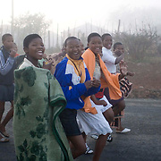 Young girls make their way to Nongoma to get transport to the Zulu royal palace in Nongoma, KwaZulu Natal, South Africa Sept 8, 2007. Thousands of virgin girls attend the annual Reed Dance at the Enyokeni palace from which the Zulu King Zwelethini may choose a bride. Photo Greg Marinovich / Bloomberg News