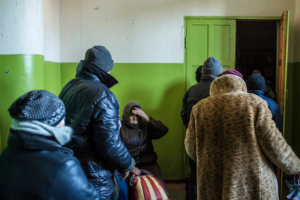MYRONIVSKYI, UKRAINE - FEBRUARY 17: Residents wait in line to receive humanitarian aid at the local House of Culture on February 17, 2015 in Myronivskyi, Ukraine. A ceasefire agreed to by Ukraine and pro-Russian rebel forces has failed to prevent fighting in the nearby town of Debaltseve, where thousands of Ukrainian troops remain and whom rebels claim to have surrounded. (Photo by Brendan Hoffman/Getty Images) *** Local Caption ***