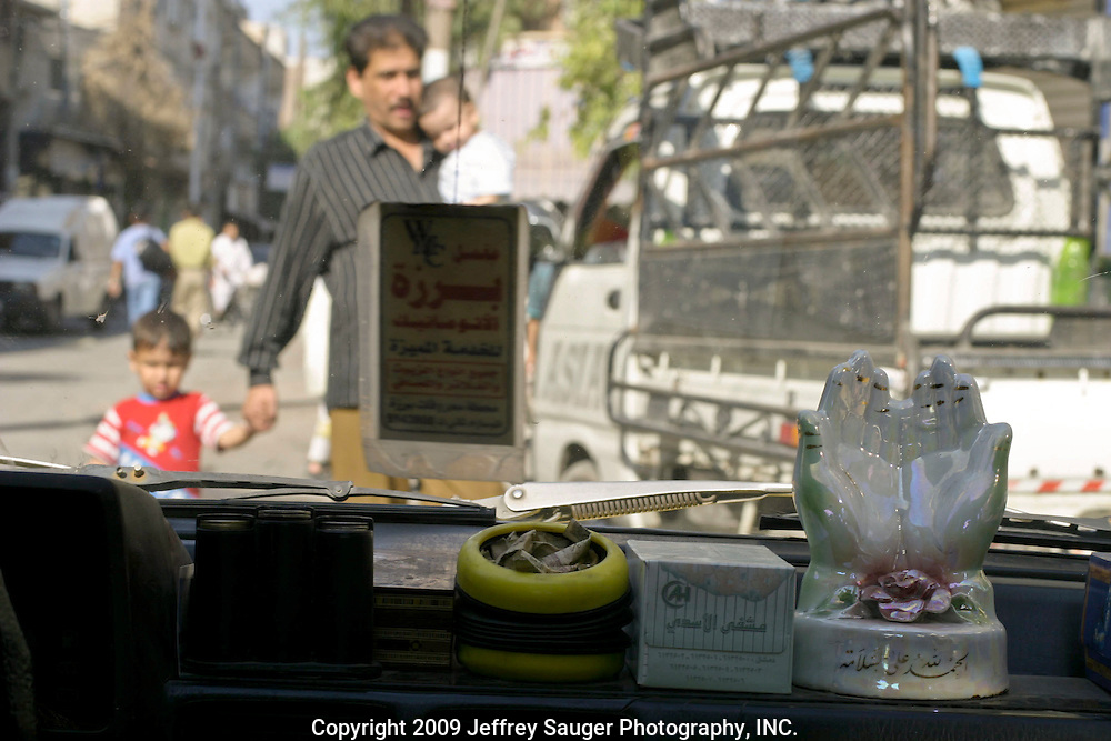 """""""Thank God for being safe,"""" reads the inscription on the bottom of the hands icon as a man and his children get out of the way of a taxi driver weaving between traffic in Damascus, Syria, Friday, July 18, 2003."""