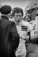 Mario Andretti, newly-crowned 1978 Formula One World Driving Champion, answers questions accompanied by Colin Chapman, founder of Lotus and team principle of the John Player Special Team Lotus-Ford. <br /> <br /> Andretti had piloted the new Lotus 79, a ground-breaking race car designed by Chapman to utilize the Bernoulli principle for creating immense ground-effect downforce from wing-shaped under-car profiles, to thoroughly dominate that year's championship. <br /> <br /> Chapman had been instrumental in the development of the modern day racing car for the past two decades. <br /> <br /> He perfected the mid-engine layout, located radiators to the sides for balance and used the engine as a stressed component to save weight, created the first monocoque Formula One chassis, provided early examples of effective wings and later ground effects downforce that, along with introducing active suspension, made the racing car a complete system rather than a collection of parts. <br /> <br /> His Hethel, England-based cars carried five drivers to Formula One World Driver's Championship titles : Jim Clark(2), Graham Hill, Jochen Rindt, Emerson Fittipaldi and Mario Andretti.
