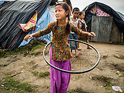 """05 AUGUST 2015 - KATHMANDU, NEPAL: A girl plays with a home made """"Hula Hoop"""" type toy in a large Internal Displaced Person (IDP) Camp in the center of Kathmandu. The camp is next to one the most expensive international hotels in Kathmandu. More than 7,100 people displaced by the Nepal earthquake in April live in 1,800 tents spread across the space of three football fields. There is no electricity in the camp. International NGOs provide water and dug latrines on the edge of the camp but the domestic waste water, from people doing laundry or dishes, runs between the tents. Most of the ground in the camp is muddy from the running water and frequent rain. Most of the camp's residents come from the mountains in northern Nepal, 8 - 12 hours from Kathmandu. The residents don't get rations or food assistance so every day many of them walk the streets of Kathmandu looking for day work.    PHOTO BY JACK KURTZ"""