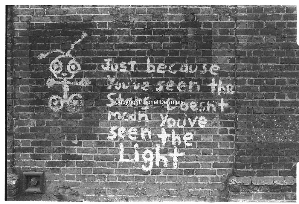"""""""Just because you've seen the stars doesn't mean you've seen the light"""", graffiti painted on a brick wall, South-East London, London street photography in 1982. Tri-X"""