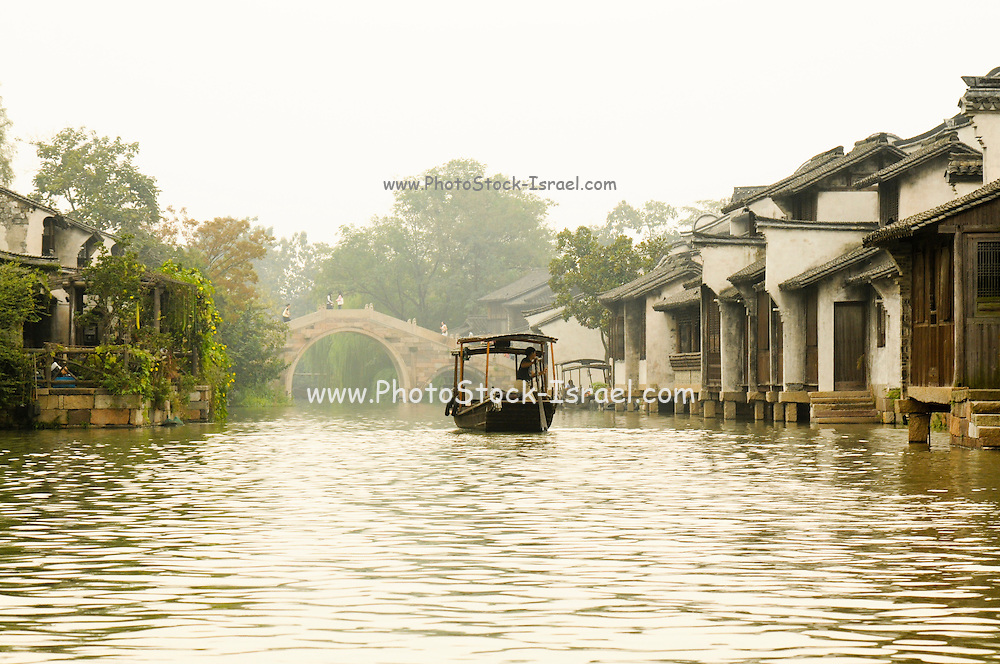 China, Zhejiang Province, Wuzhen a two-thousand-year village proud of it's ancient stone bridges floating on mild water, its stone pathways between the mottled walls and its delicate wood carvings.