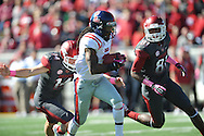 Ole Miss defensive back Charles Sawyer (3) blocks a punt by Arkansas punter Dylan Breeding (14) and is chased by Arkansas wide receiver Demetrius Wilson (81) at War Memorial Stadium in Little Rock, Ark. on Saturday, October 27, 2012. Ole Miss won 30-27...