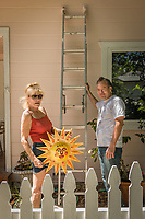 """""""Growing up in the north of Norway, I always dreamed of living in a sunny spot...I found it here in Calistoga.  This sun showed up in my clay and promised me a sunny future.""""   -Torlid Roberts with her partner, Ernest Rankin, prepare to hang her ceramic sun on the front their home on Washington Street in Calistoga."""