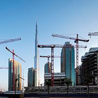 United Arab Emirates, Dubai, Burj Khalifa, the tallest building in the world, looms above construction sites and cranes at sunrise