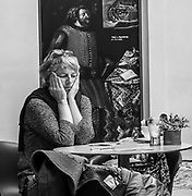 A woman sits by herself, focused on her inner world, at a museum cafe in Prague's Castle.