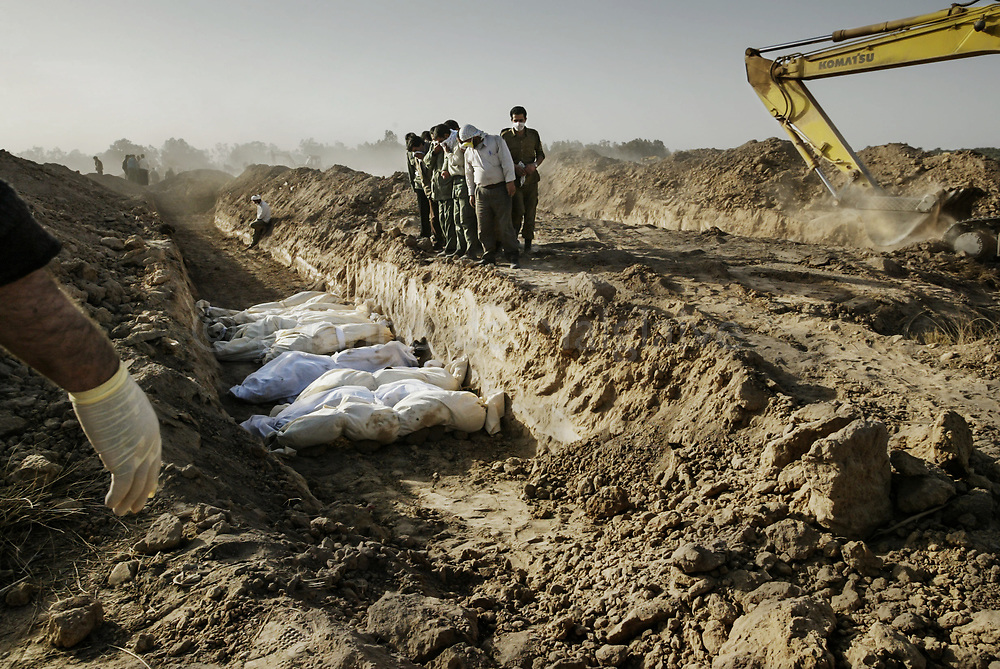 At the cemetery, mass grave trenches are excavated in haste with construction equipment to bury thousands of victims. 29 December 2003. On December 26, 2003 at 05:27 AM local time, a 6.6 Richter magnitude earthquake struck southeastern Iran, killing more than 26,000 in the city of Bam and destroying 85% of buildings.