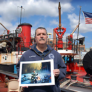 Firefighter Brian McCrick displays Neville Elder's photograph of him in the ruins of the World Trade Center, ten years after the terrorist attacks.