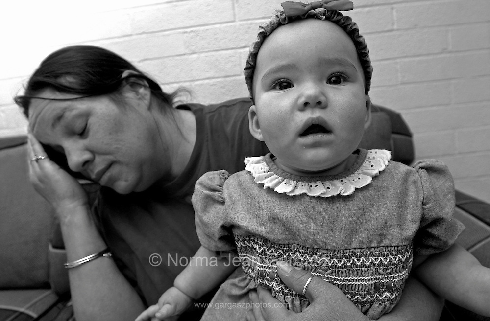 A young girl waits with her mother at a shelter for the homeless after the family had financial difficulties in Tucson, Arizona, USA.