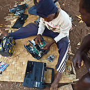 26 September 2011, Alges, Matala, Angola. Electronics repair work under the tree. Canals leading of the Cunene river for irrigation purposes, becomes a lethal channel for the spread of cholera. Households close to the canal use the water for household purposes and open defecation near these water sources, lead to contamination later on. Villages who have erected water tanks and water suply directly to households, are generally protected from the spread of disease. Alges's water tanks supply 2,000 households (approximately 10,000 people).