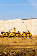 Several scrapers and a tracked backhoe await the next days work on a new warehouse being built near Joliet, IL.