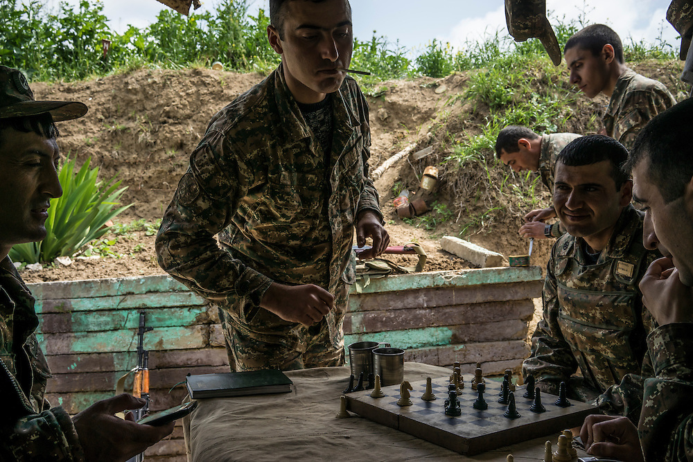 AGDAM, NAGORNO-KARABAKH - APRIL 21: Members of the armed forces of Nagorno-Karabakh play checkers using a chess set at their post along the line of contact with Azerbaijani forces in the eastern direction on April 21, 2015 near the town of Agdam, Nagorno-Karabakh. Since signing a ceasefire in a war with Azerbaijan in 1994, Nagorno-Karabakh, officially part of Azerbaijan, has functioned as a self-declared independent republic and de facto part of Armenia, with hostilities along the line of contact between Nagorno-Karabakh and Azerbaijan occasionally flaring up and causing casualties. (Photo by Brendan Hoffman/Getty Images) *** Local Caption ***