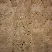 Detail in the British Museum of an Assyrian formal scene, from, about 865-860 BC from the ancient city of Nimrud. In one scene the king appears as conqueror with bow and arrows, flanked by guman attendants.