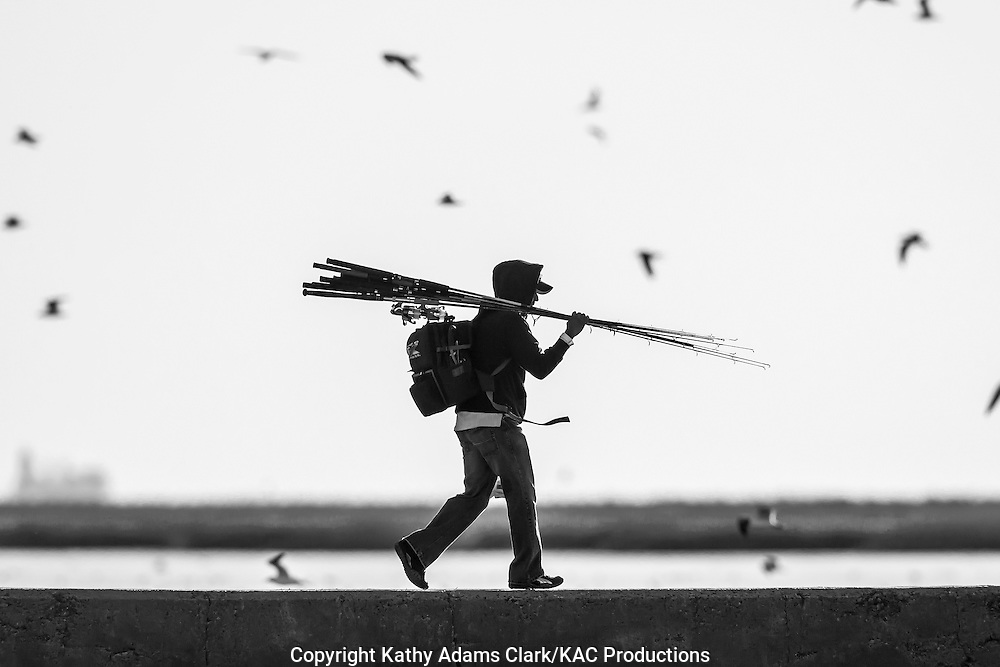 Fisherman carrying gear walking in Galveston, Texas. Black and white conversion