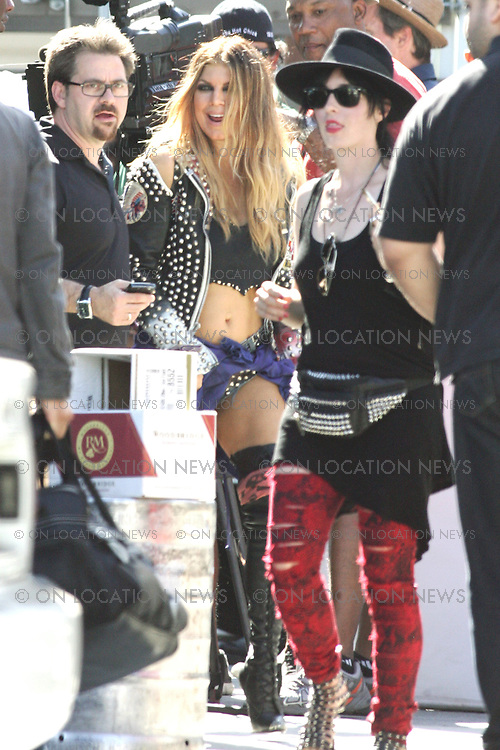 """August 27th, 2010  Hollywood CA, ***EXCLUSIVE*** Fergie and Slash film a music video together for """"Beautiful Dangerous"""" before performing together live at the third annual Sunset Strip Music Festival in Hollywood. Fergie and Slash filmed scenes for the video at the famous Jumbo's Clown Room burlesque strip bar where a blond  haired Fergie performed as a stripper with Slash in the audience. Another scene took place at a cheap hotel nearby. In that scene Slash was tied to a bed and at the mercy of Fergie the stripper! On the wall of the hotel room was seen all kinds of Slash memorabilia from over the years suggesting that Fergie was obsessed with Slash. Photo by Danny Mayer/Eric Ford/ On Location News 818-613-3955 info@onlocationnews.com"""
