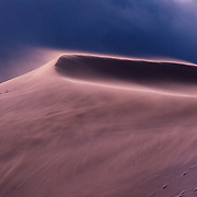 Wind blown sand dune with storm clouds