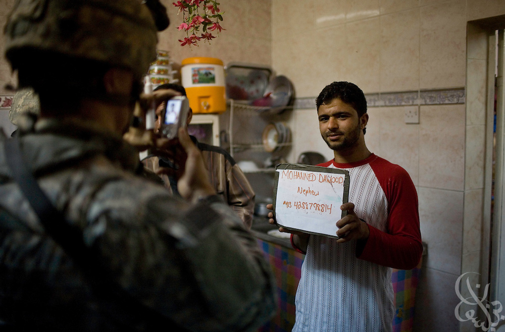 A 2-325 82nd Airborne Division soldier takes a digital  photo of an Iraqi man during a patrol in the district of Sha'ab in Baghdad, Iraq June 04, 2007. Soldiers from the unit searched several Iraqi homes and took ID photos of all military age males who resided in them. ...
