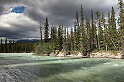 A patch of sun breaks through the clouds over a river near Jasper, Alberta, Canada