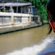 Girl riding along the canal, Bangkok, Thailand