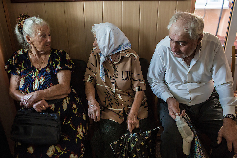 SARTANA, UKRAINE - AUGUST 29, 2015: Elderly residents await the start of humanitarian aid distribution in Sartana, Ukraine. The village of Sartana, on the northeastern outskirts of Mariupol, has been relatively close to the front line between Ukrainian and pro-Russian rebel forces, with many incidents of shelling damaging homes and injuring or killing civilians. CREDIT: Brendan Hoffman for The New York Times