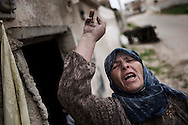 SYRIA, Idlib province, Taftanaz: A Syrian woman who lost two sons that were killed by Al Assad forces, shouts anti regime slogans in front of her burned house, on April 11, 2012. ALESSIO ROMENZI