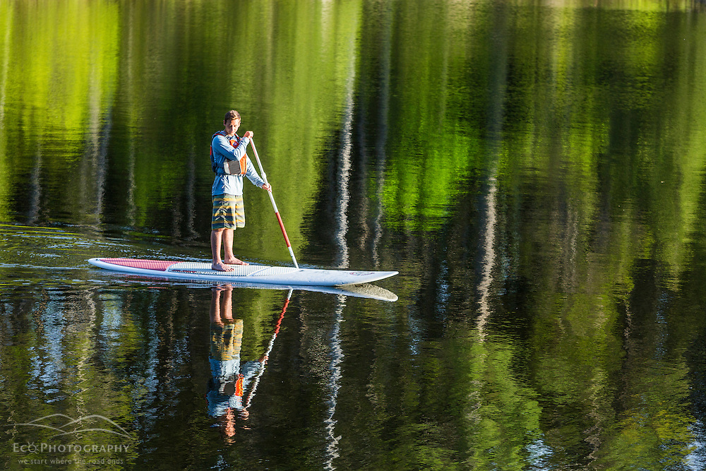 A man paddleboarding on Long Pond near the Appalachian Mountain Club's Gorman Chairback Lodge. Near Greenville, Maine.