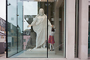A devoted young girl holds the hand of a Jesus statue in the foyer of The Church of Jesus Christ of Latter-day Saints (Mormons) in central London, England.