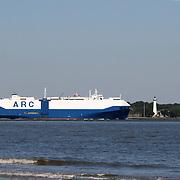 Cargo ship passing St. Simon's Island lighthouse on way to sea