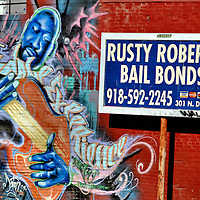 Guitar Player Mural by Anthony Carrera and Bail Bond Sign in Tulsa, Oklahoma<br /> This mural on a red brick wall in Tulsa, Oklahoma, is called &ldquo;The Tisalale Experience.&rdquo; The guitar player was painted by artist and tattoo shop owner Anthony &ldquo;Eratick&rdquo; Carrera. He tends to adorn walls and human bodies with equally flamboyant designs and colors. The &ldquo;Rusty Roberts Bail Bonds&rdquo; sign is a real advertisement that shared the alley with the street art.
