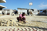 A woman makes food from dried clay just outside of the ruins of Fort Dimanche.