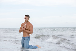 shirtless man in the ocean holding a seashell to his chest