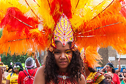 """London, August 24th 2014. A young woman's feathered headress makes for  a colourful display  as thousands of Londoners of all races and cultures attend Notting Hill Carnival's """"Family friendly"""" day ahead of the main carnival on August Bank Holiday Monday."""