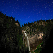 Comet Falls, so named because it resembles a comet's tail, glows underneath the night sky. The waterfall, which is located in Mount Rainier National Park, Washington, is lit by the full moon. Comet Falls, at 320 feet (98 meters), is one of the tallest waterfalls in the park..