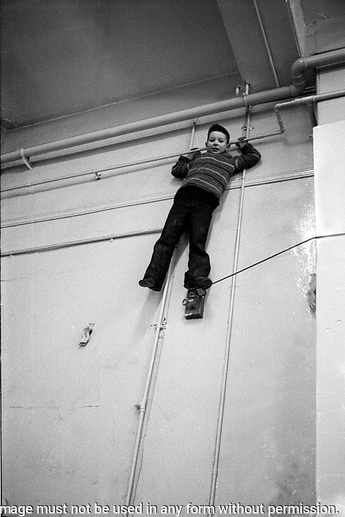 Young child at free school climbing the wall