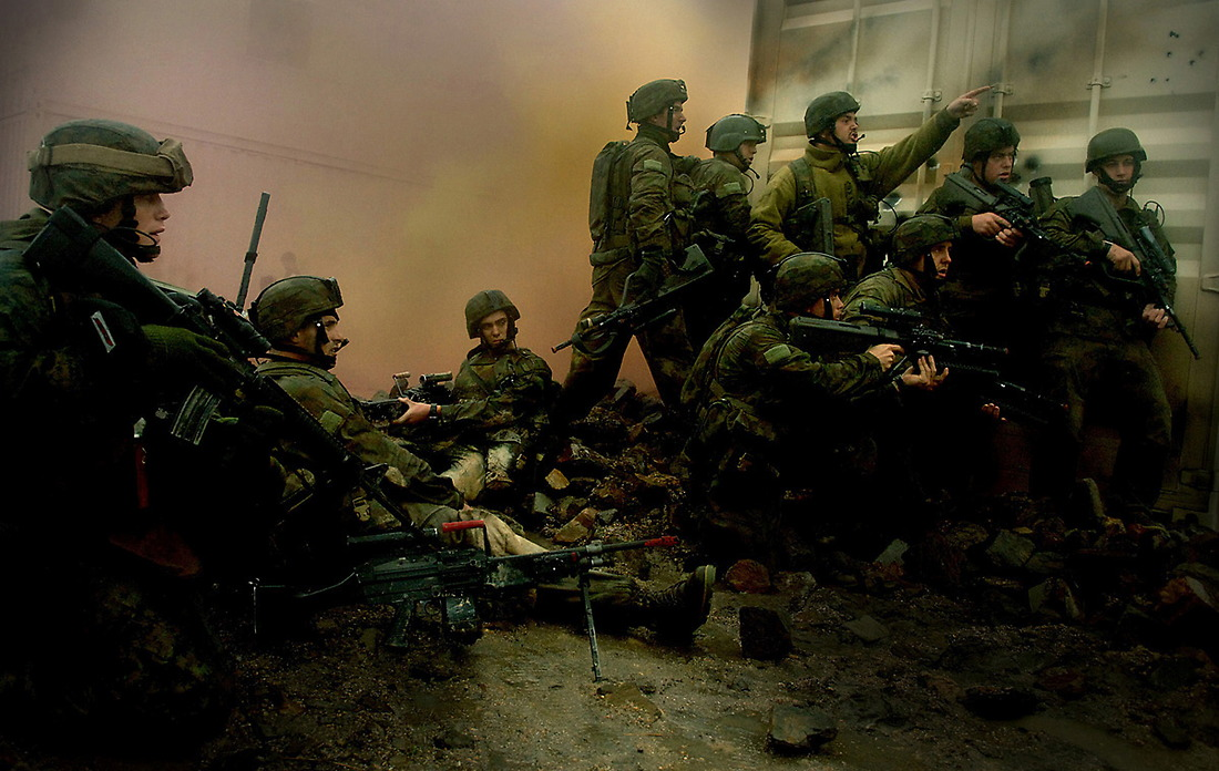 Pinned down behind a building, a platoon of soldiers from the Australian army wait for suppression fire and smoke before advancing further in Camp Raspberry. — © TSgt. Jeremy T. Lock/