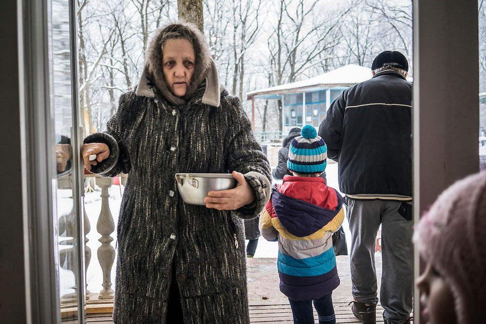 Residents arrive at a communal dining hall, dishes in tow, for lunch at Romashka, a summer camp where several hundred people live after being displaced by fighting in Eastern Ukraine on Friday, February 13, 2015 in Kharkiv, Ukraine.