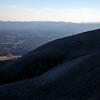 A hiker climbs up a hillside before sunset near Bee Canyon Park as methane gas leaks from the SoCalGas Aliso Canyon Storage Facility well SS-25 in the Porter Ranch neighborhood of Los Angeles, California on Wednesday, December 30, 2015. The Aliso Canyon gas leak (also called Porter Ranch gas leak) was a massive natural gas leak that started on October 23, 2015. According to Wikipedia, an estimated 1,000,000 barrels per day was released from a well within the underground storage facility in the Santa Susana Mountains near Porter Ranch. The second-largest gas storage facility it belongs to the Southern California Gas Company (SoCalGas), a subsidiary of Sempra Energy. On Jan. 6, 2016, Governor Jerry Brown issued a State of Emergency. The Aliso gas leak carbon footprint is said to be larger than the Deepwater Horizon leak in the Gulf of Mexico. On Feb. 11, 2016 the gas company reported that it had the leak under control. On Feb. 18 state officials announced that the leak was permanently plugged. An estimated 97,100 tonnes of methane and 7,300 tonnes of ethane was released into the atmosphere, making it the worst natural gas leak in U.S. history in terms of its environmental impact. © 2015 Patrick T. Fallon
