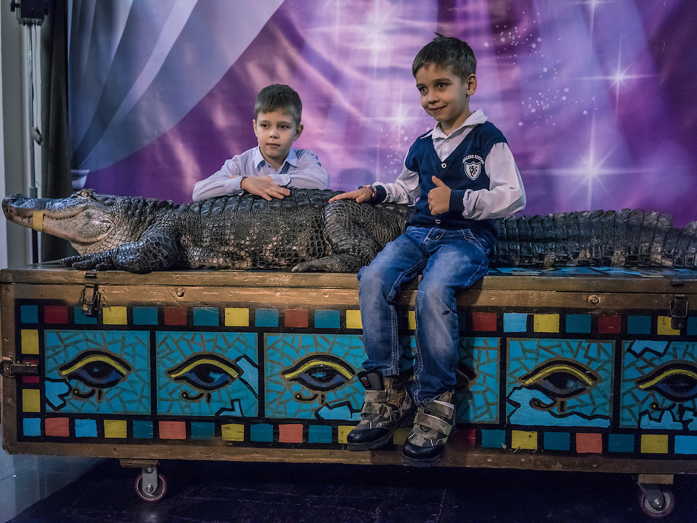 Boys attending the Belarus State Circus pose for a picture with a crocodile named Marta on Wednesday, November 25, 2015 in Minsk, Belarus.