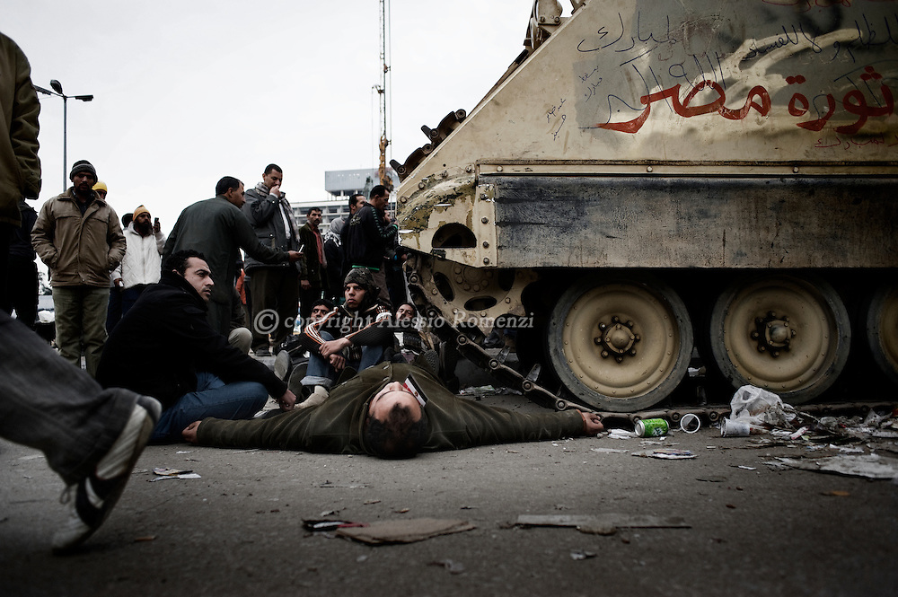 EGYPT, Cairo : Egyptian anti-government protesters calling for the ouster of President Hosni Mubarak block an Egyptian army armoured personnel carrier (APC) at Tahrir Square in Cairo on February 5, 2011. Protesters sat on the ground around some of the tanks to prevent the troops pulling out and leaving the square vulnerable to the feared interior ministry riot police or militants loyal to Mubarak's ruling National Democratic Party.© ALESSIO ROMENZI
