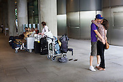 Young lovers embrace in bus station at Arrivals after long absence aprt at Heathrow's terminal 5.