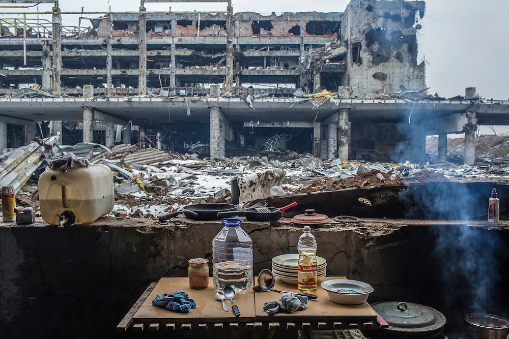 Domestic items are spread around a living area for Russian-backed rebels stationed in a parking garage with a view of the destroyed terminal of the Donetsk Airport on Tuesday, March 22, 2016 in Donetsk, Ukraine.