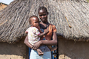 Rebecca Morris is pictured standing in front of her tukul (a hut with a thatched roof), which she fled from during the July 2016 fighting in Juba. She came back recently with her mother. Her father was killed during the July confrontation and she is saddened by his death. He was also helping her financially to attend school and it is now difficult for her to continue. She feels safer after deminers began clearing the area and making it safe for her to be back in her home.<br /> <br /> Photo: UNMAS/ Martine Perret