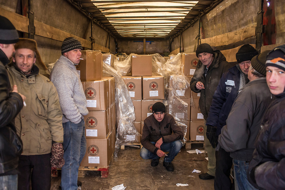 MNOGOPOLYE, UKRAINE - JANUARY 24, 2015: Local residents take a break while unloading a delivery of humanitarian aid by the International Committee of the Red Cross in Mnogopolye, Ukraine. ICRC aid deliveries are planned for the area approximately once per month, and supply food and hygiene items for more than one thousand people. CREDIT: Brendan Hoffman for The New York Times
