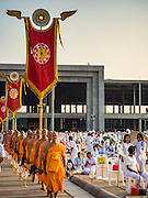 "11 FEBRUARY 2016 - KHLONG LUANG, PATHUM THANI, THAILAND: Buddhist monks walk into the pagoda during the Makha Bucha Day service at Wat Phra Dhammakaya.  Makha Bucha Day is a public holiday in Cambodia, Laos, Myanmar and Thailand. Many people go to the temple to perform merit-making activities on Makha Bucha Day, which marks four important events in Buddhism: 1,250 disciples came to see the Buddha without being summoned, all of them were Arhantas, or Enlightened Ones, and all were ordained by the Buddha himself. The Buddha gave those Arhantas the principles of Buddhism. In Thailand, this teaching has been dubbed the ""Heart of Buddhism."" Wat Phra Dhammakaya is the center of the Dhammakaya Movement, a Buddhist sect founded in the 1970s and led by Phra Dhammachayo. Makha Bucha Day is one of the most important holy days on the Thai Buddhist calender.      PHOTO BY JACK KURTZ"