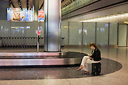 Lone lady awaiting her luggage from domestic baggage reclaim carousel at Heathrow's Terminal 5.
